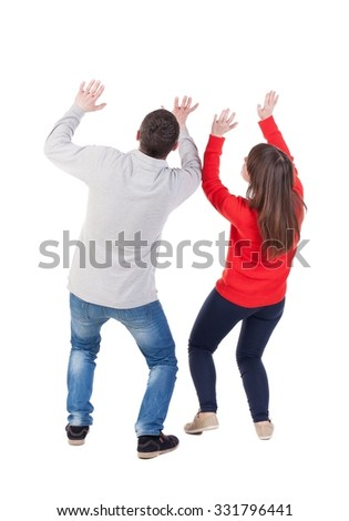 Back view of young embracing couple (man and woman) Ducked protecting yourself from the danger of hands.  beautiful friendly girl and guy together. Rear view people collection.  - stock photo