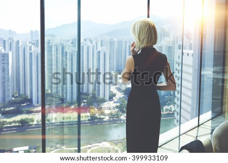 Back view of young entrepreneur is calling via cell telephone, while is standing in her private office against window with view of developed business district with high skyscrapers.Copy space for text - stock photo