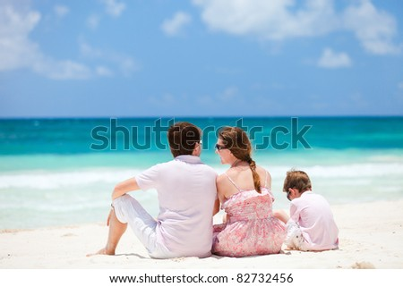 Back view of young family at Caribbean beach - stock photo