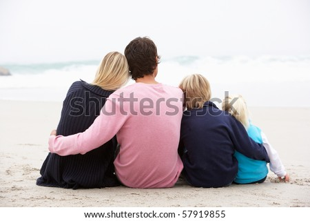 Back View Of Young Family Sitting On Winter Beach - stock photo