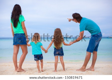 Back view of young family with two daughters at exotic beach on sunny day - stock photo