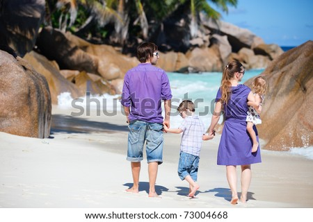 Back view of  young family with two kids walking along tropical beach - stock photo