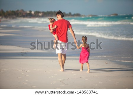 Back view of young father and his cute daughters walking along the sea - stock photo