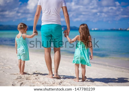 Back view of young father and his two little kids walking by the sea - stock photo