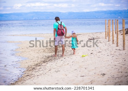Back view of young father and little girl walking by the sea - stock photo