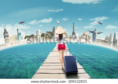 Back view of young girl carrying luggage on the bridge to trip the worldwide monument - stock photo