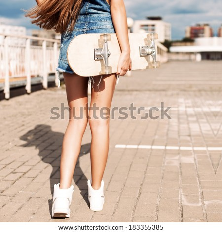 back view of young girl in short overalls with long legs and long silky hair holding skateboard - stock photo