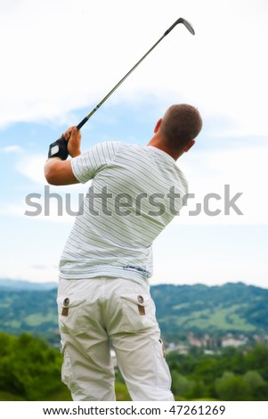 Back view of young golfer in swing pose.