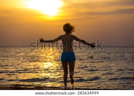 Back view of young happy woman in blue swimwear running with stretched arms into the sea towards colorful sunrise or sunset sky, basking in warm sunlight, rising water splashes - stock photo