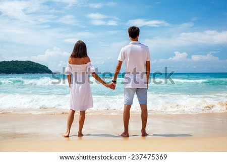 Back view of young lovely couple standing on sandy beach - stock photo