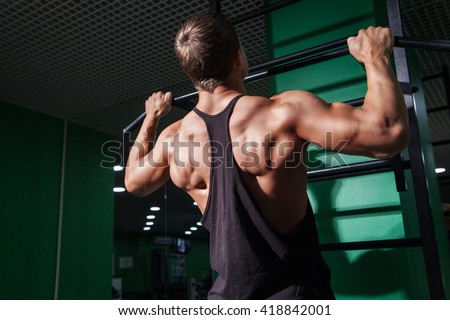 Back view of young man doing pull ups