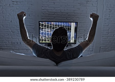 back view of young man home alone watching soccer or football game in television enjoying and celebrating goal and victory gesturing with fist sitting on the sofa happy and excited - stock photo