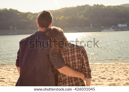 Back view of young man huging his girlfriend at the beach - stock photo