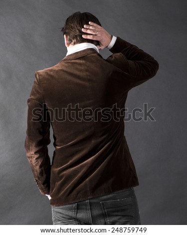 Back view of young man on a dark background - stock photo