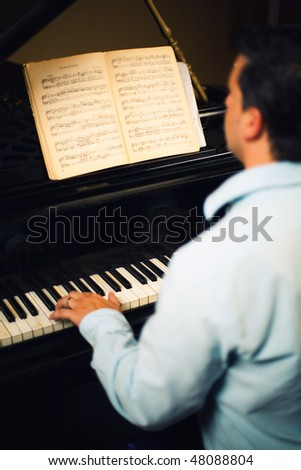 Back view of young man playing the piano. - stock photo