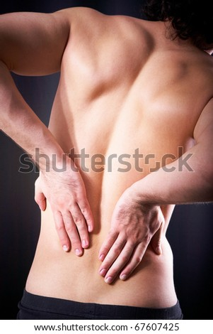 Back view of young man touching aching back - stock photo