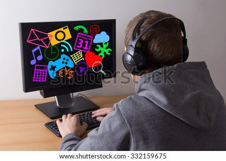 back view of young man using a computer and listening music at home - stock photo