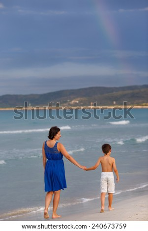 Back view of young mother and her son walking along tropical beach - stock photo
