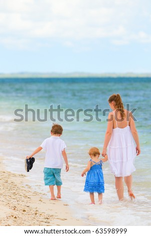 Back view of young mother and her two kids walking along tropical white sand beach - stock photo