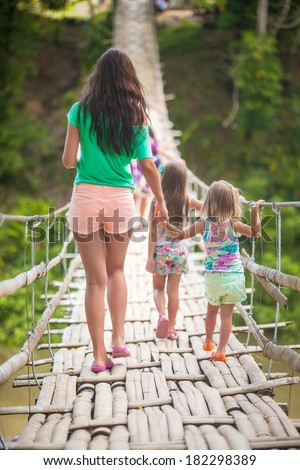 Back view of young mother with her little girls on suspension bridge over the River Loboc, Philippines