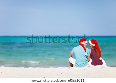 Back view of young romantic couple in red Santa hats sitting on beach and looking to each other - stock photo