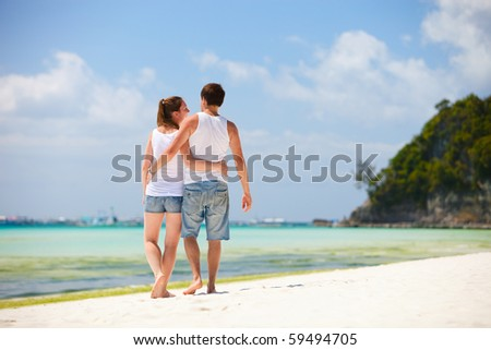 Back view of young romantic couple walking along tropical beach - stock photo