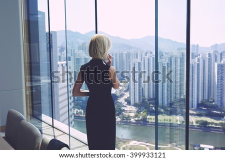 Back view of young successful businesswoman is having mobile phone conversation with managing director her company, while is standing in office interior near window with cityscape view and copy space - stock photo