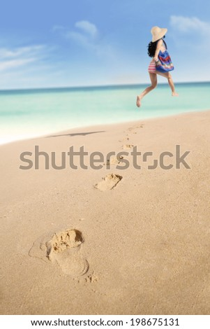 Back view of young woman in bikini jumping at beach while holding sandals and sunglasses