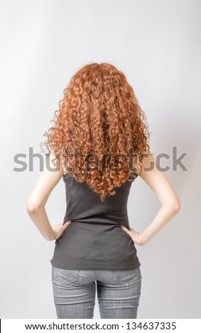 Back view of young woman in jeans and  black shirt points at wall. Rear view - stock photo