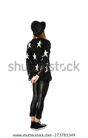 Back view of young woman in leather pants and hat looking at wall. The rear view. Isolated over white background. - stock photo