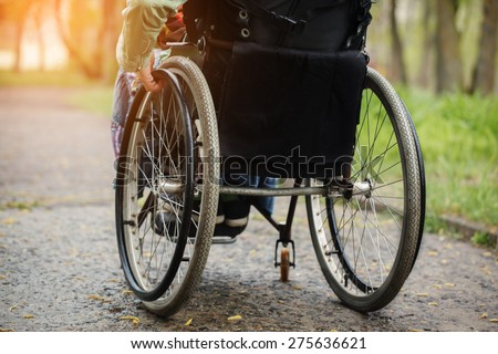 Back view of young woman in  wheelchair during walk in park  in sunny day - stock photo