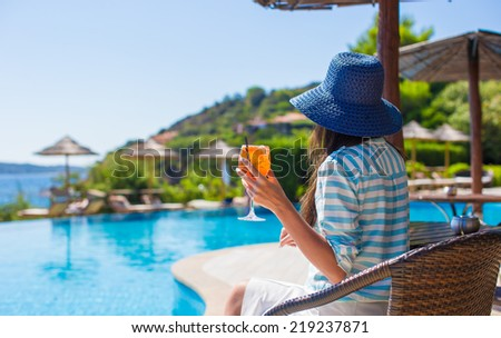 Back view of young woman sitting in tropical cafe near swimming pool - stock photo