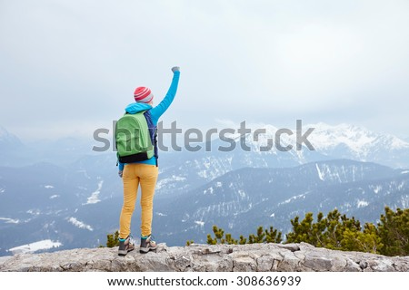 Back view of young woman wearing pink hat, blue jacket, green backpack, yellow pants and hiking boots raising her hand against winter mountains celebrating successful climb - goal concept - stock photo
