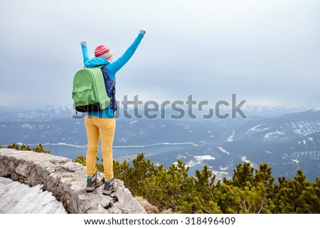 Back view of young woman wearing pink hat, blue jacket, green backpack, yellow pants and hiking boots raising her hands against winter mountain valley celebrating successful climb - goal concept - stock photo