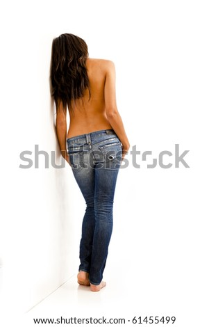 Back view of young woman with bare top wearing worn jeans - stock photo