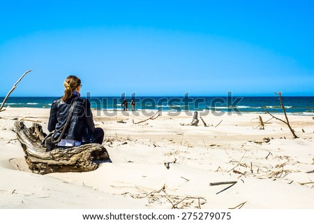 Back view of young woman with blond hair, sitting on a  wooden log, sitting on the beach, facing ocean, wearing black leather jacket - stock photo