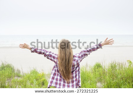 Back view of young woman with long blond hair and outstretched arms on empty beach facing ocean wearing plaid shirt - stock photo