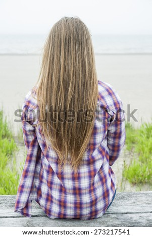 Back view of young woman with long blond hair sitting on misty beach facing ocean wearing plaid shirt - stock photo