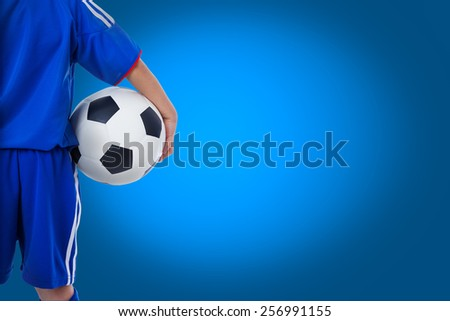 Back view of youth soccer player in blue uniform and little kid holding a ball. Some space for input text message on blue background - stock photo