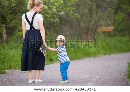 Back view on beautiful woman with flowers and a cute toddler boy walking in the park on a summer day. Happy family enjoying walk outdoors. Young mother with adorable small child. - stock photo