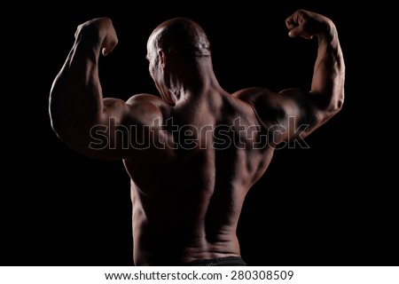 back view on muscular bald man posing on a black background - stock photo