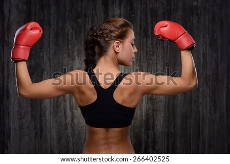 Back view photo of young mixed race sporty woman wearing black tracksuit for training with red boxing gloves. Fitness concept  - stock photo