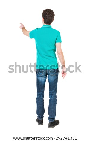Back view pointing young men in  shirt and jeans. Young guy  gesture. Rear view people collection. backside view person. Isolated over white background. guy in a stylish T-shirt shows the left hand  - stock photo