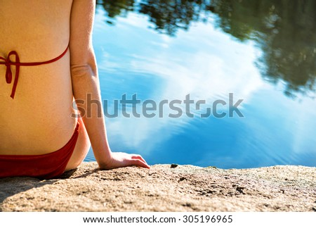 Back view portrait of a beautiful relaxed woman on the beach with blue water background - stock photo