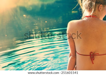 Back view portrait of a beautiful relaxed woman on the beach with blue water background. Colorized like instagram filter. - stock photo
