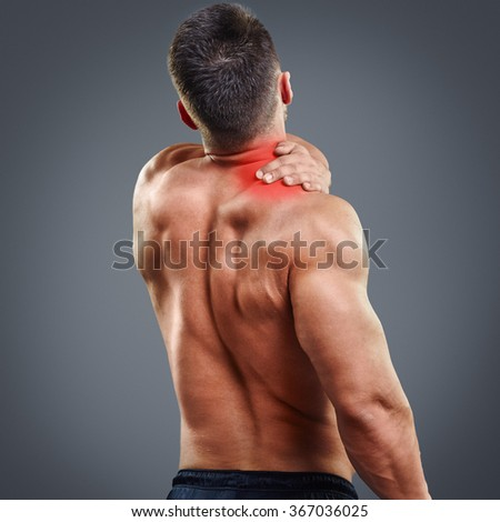 Back view portrait of a Bodybuilder with neck pain over gray background. Concept with highlighted glowing red spot. - stock photo
