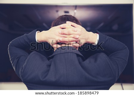 Back view portrait of a businessman standing with arms behind head - stock photo