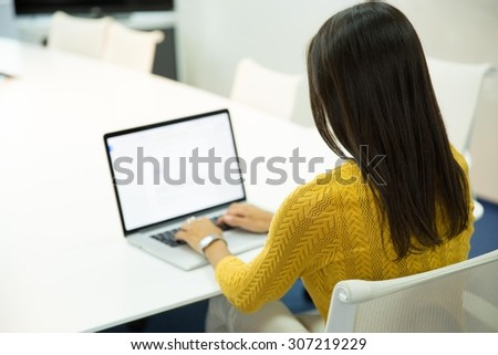 Back view portrait of a casual businesswoman working on laptop in office