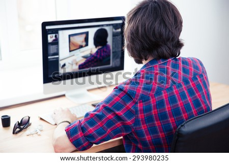 Back view portrait of a male photo editor working on computer in office - stock photo
