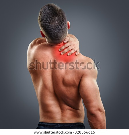 Back view portrait of a man with neck pain over gray background. Concept with highlighted glowing red spot. - stock photo